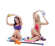 Two smiling young female athletes posing in studio royalty free stock photos