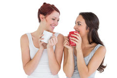 Two smiling young female friends drinking coffee Stock Photos