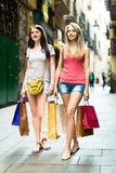 Two smiling young girl going shopping. In European city Stock Photos
