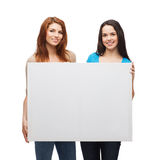 Two smiling young girls with blank white board Royalty Free Stock Image