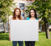 Two smiling young girls with blank white board Royalty Free Stock Photos