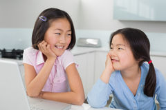Two smiling young girls with laptop in kitchen Stock Photos