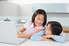 Two smiling young girls with laptop in kitchen Royalty Free Stock Photo