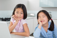 Two smiling young girls with laptop in kitchen Stock Image