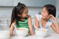 Two smiling young girls sitting with cereal bowls in kitchen Stock Photography