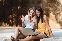 Two smiling young girls using laptop at the park. Laughing, chatting stock image