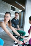 Two smiling young people exercise in gym. royalty free stock photos