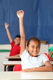 Two smiling young school children arms raised in c. Two happy young primary school children signalling they know the answer with hands raised in class - Canon 5D Royalty Free Stock Photos