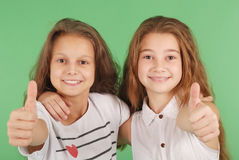Two smiling young school girls showing thumbs up Royalty Free Stock Image