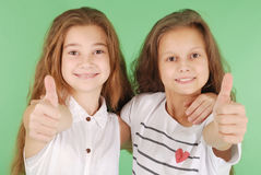 Two smiling young school girls showing thumbs up. Isolated on green background Stock Photo
