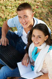 Two smiling young students outdoors. Two students sitting in park on grass with computer notebook Royalty Free Stock Photo