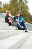 Two smiling young students outdoors Stock Photos