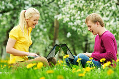 Two smiling young students outdoors with computers Stock Image