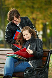 Two smiling young students studying outdoors Royalty Free Stock Images