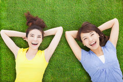 Two smiling  young woman lying  on meadow Royalty Free Stock Photos