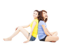 Two smiling  young woman sitting and back to back Stock Images