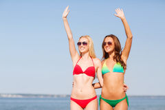 Two smiling young women on beach Stock Image