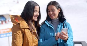Two smiling young women checking a phone. Two cute smiling young adult women in long black hair brown and blue jackets looking at a cell phone while standing in stock video