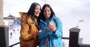 Two smiling young women checking a phone. Two cute smiling young adult women in long black hair brown and blue jackets looking at a cell phone while standing in stock footage