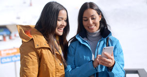 Two smiling young women checking a phone Stock Photos