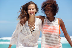 Two smiling young women enjoying the beach Royalty Free Stock Image