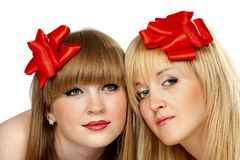 Two smiling young women with gift red bow Royalty Free Stock Images