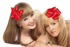 Two smiling young women with gift red bow. Portrait of two smiling young women with gift red bow over white background Royalty Free Stock Photography