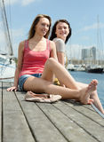 Two smiling young women sitting on the berth Royalty Free Stock Images