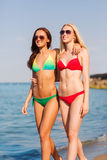 Two smiling young women walking on beach Royalty Free Stock Photos