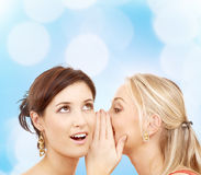 Two smiling young women whispering gossip Royalty Free Stock Image