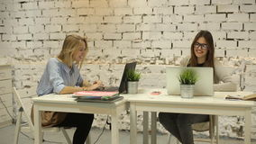 Two smilling businesswomen working on laptop at office. And smilling stock footage