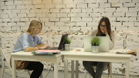 Two smilling businesswomen working on laptop at office. And smilling stock video footage