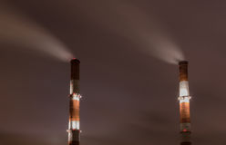 Two smoke stack against sky Royalty Free Stock Photos