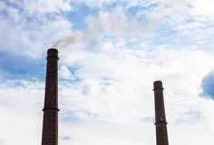 Two smoke stacks of the industrial plant against the cloudy sky Royalty Free Stock Photography
