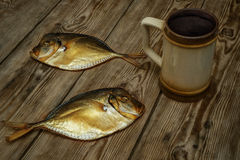 Two smoked fish and beer mug on a wooden table Stock Images