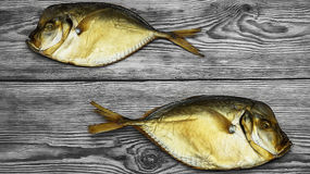 Two smoked fish on the wooden table Stock Images