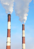 Two smoking chimneys of power plant stock image