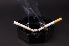 Two smoking cigarettes Royalty Free Stock Photography