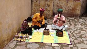 Two Snake Charmers Captivate Cobras. Two snake charmers blow on pungis, flute-like instruments, entrancing cobras out of baskets at the Amber Palace in Rajasthan stock footage