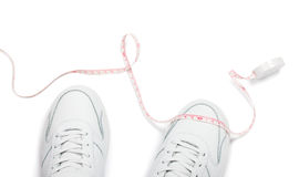 Two sneakers and meter over white background Royalty Free Stock Photo
