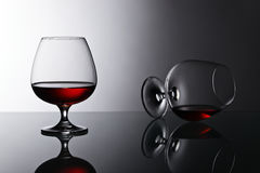 Two snifters of brandy on glass table Stock Image