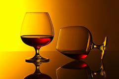 Two snifters of brandy on glass table Royalty Free Stock Images