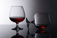 Two snifters of brandy on glass table Royalty Free Stock Photo