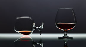 Two snifters of brandy on glass table Royalty Free Stock Photography