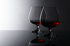 Two snifters of brandy on glass table Royalty Free Stock Photos
