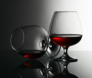 Two snifters of brandy on glass table Stock Photography