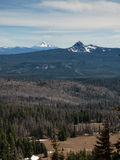 Two snow capped mountain peaks. The two snow capped mountain peaks rise from the forested hills. Mt. McLoughlin, Oregon Royalty Free Stock Images