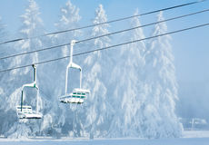 Two snow-covered chairs of not working chair-lift Royalty Free Stock Photos