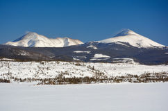 Two Snow Covered Mountain Peaks on a Cold Winter Day.  Stock Image