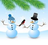 Two snow men with a bird bullfinch Stock Photo